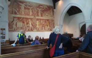 Walkers admiring ancient mural in Chaldon Church depicting heaven and hell